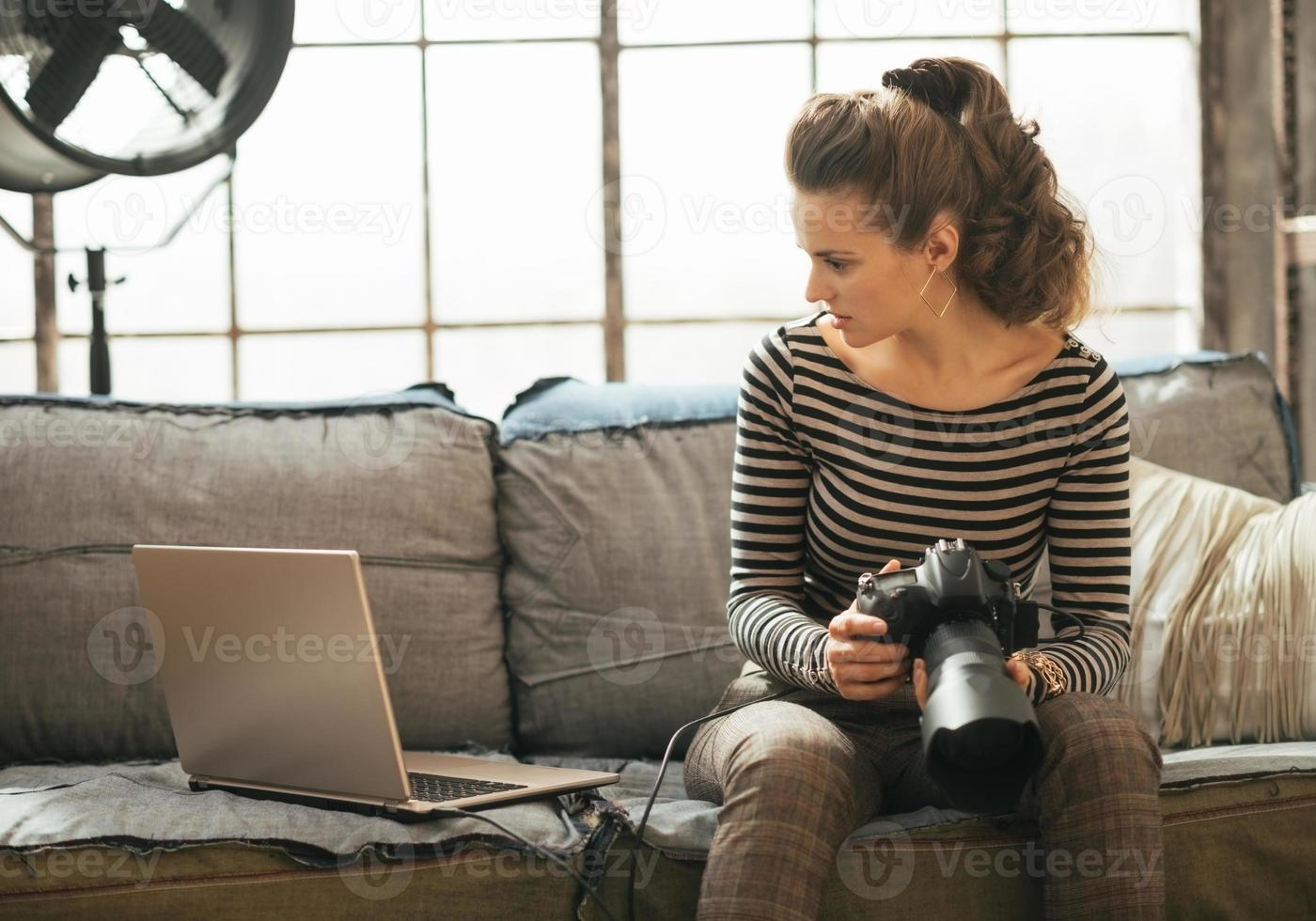 mujer joven con moderna cámara de fotos dslr usando laptop