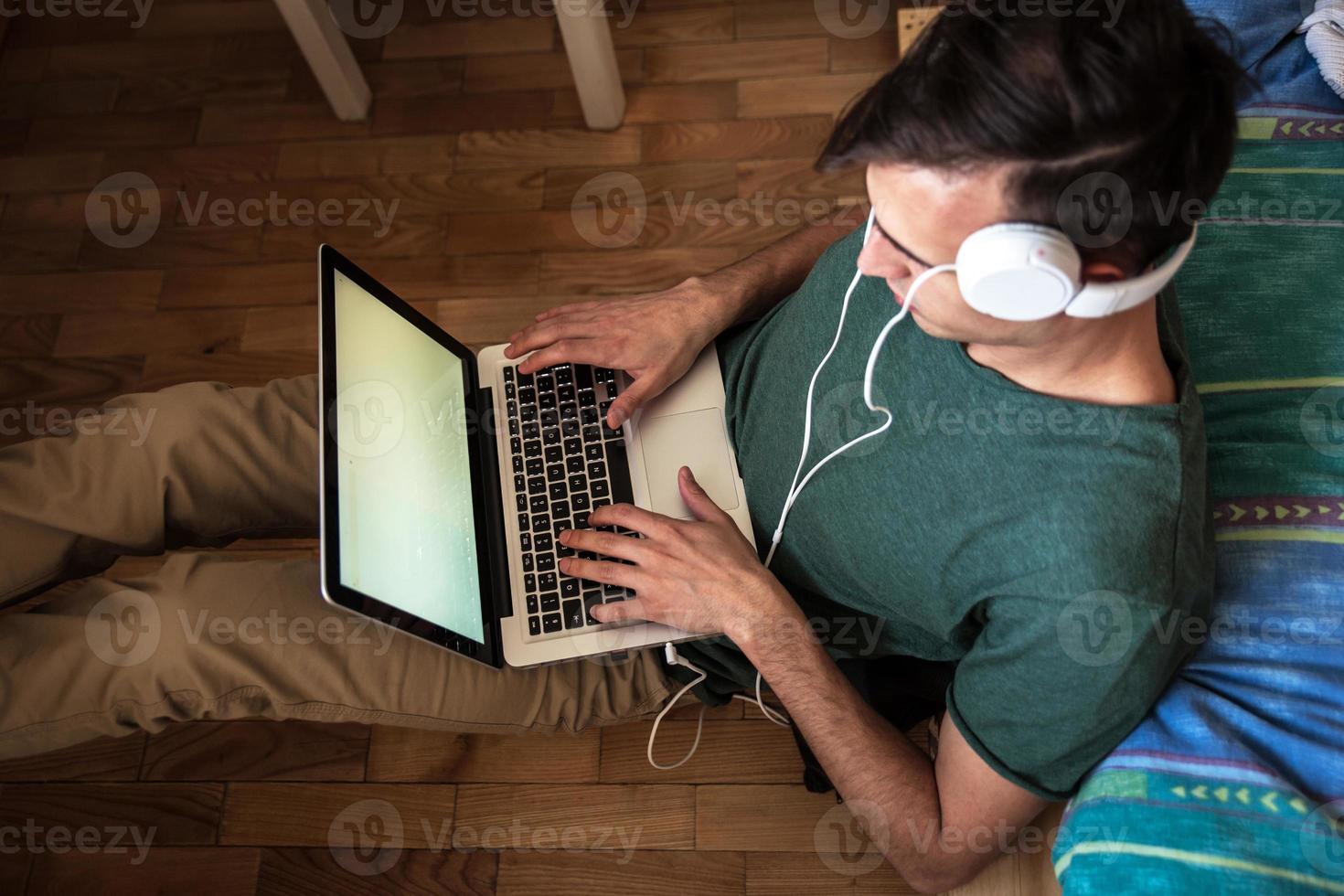 Joven trabajando en su casa en la computadora portátil. foto