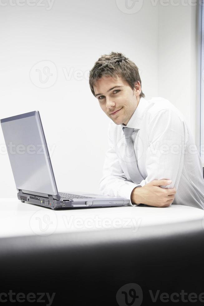 empresario sonriente, sentado con la computadora portátil en el escritorio foto