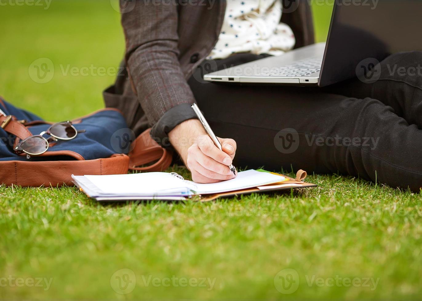 young fashion male student sitting on grass photo