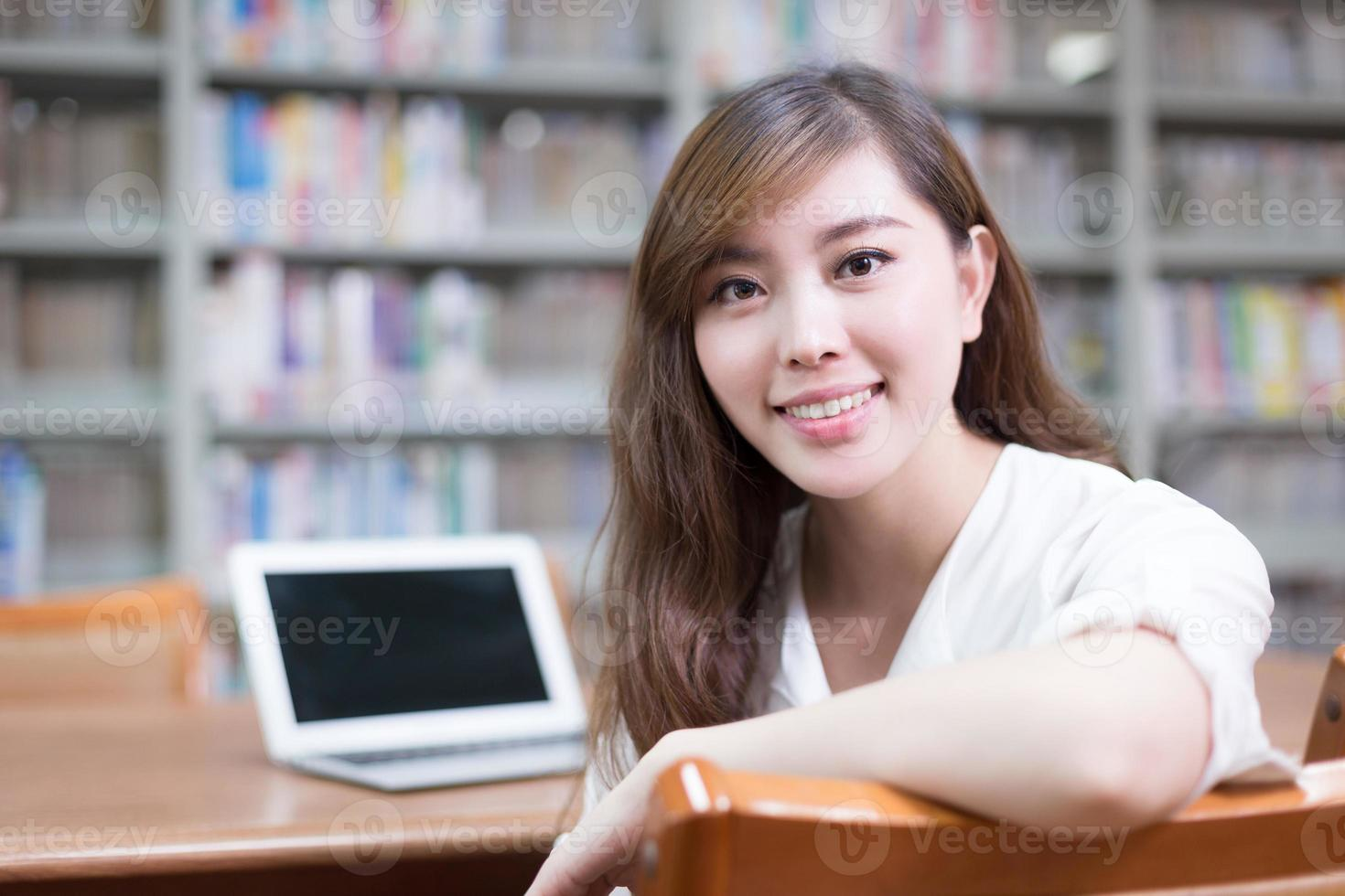 Hermosa estudiante asiática usando laptop para estudiar en la biblioteca foto