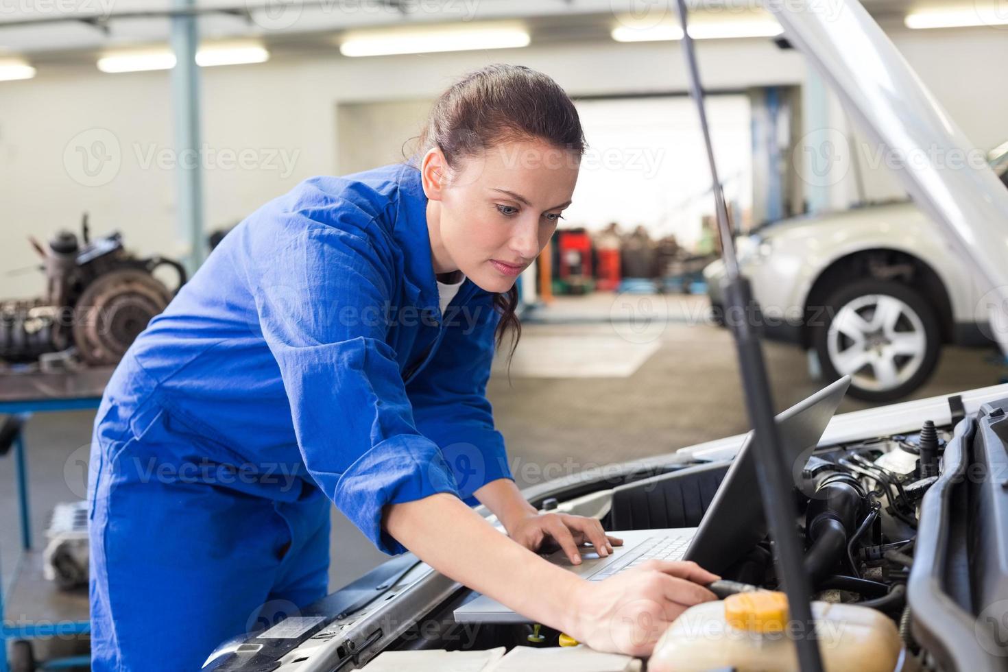 Mechanic using laptop on car photo