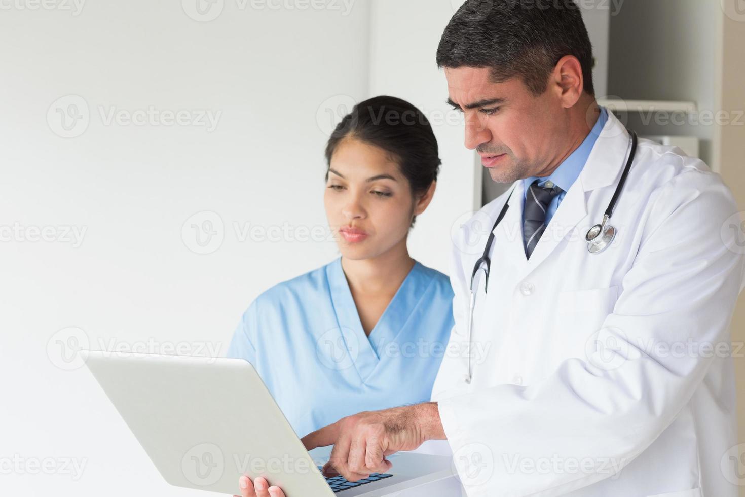Doctor showing laptop to nurse photo