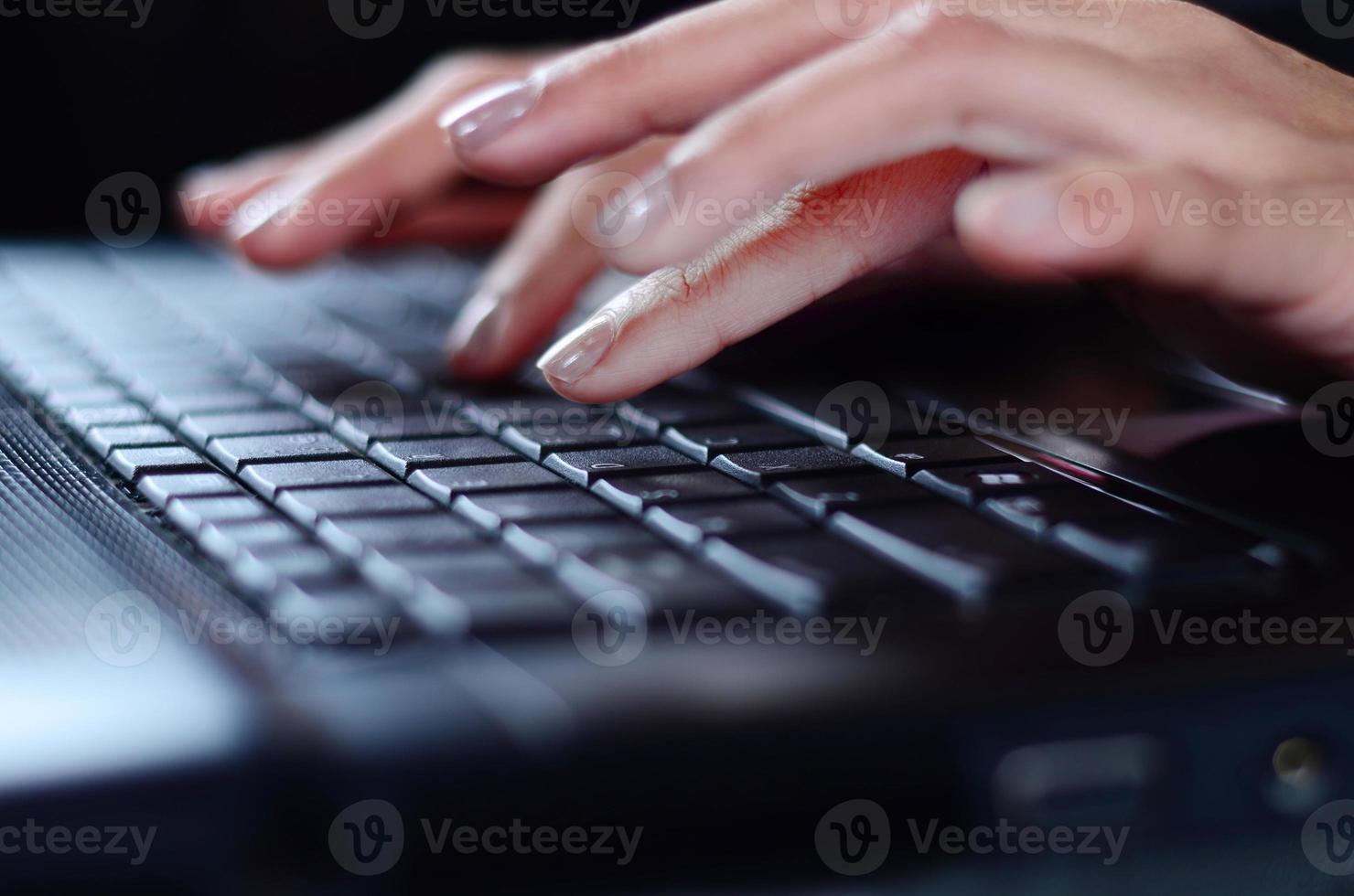 manos de mujer escribiendo en la computadora portátil foto