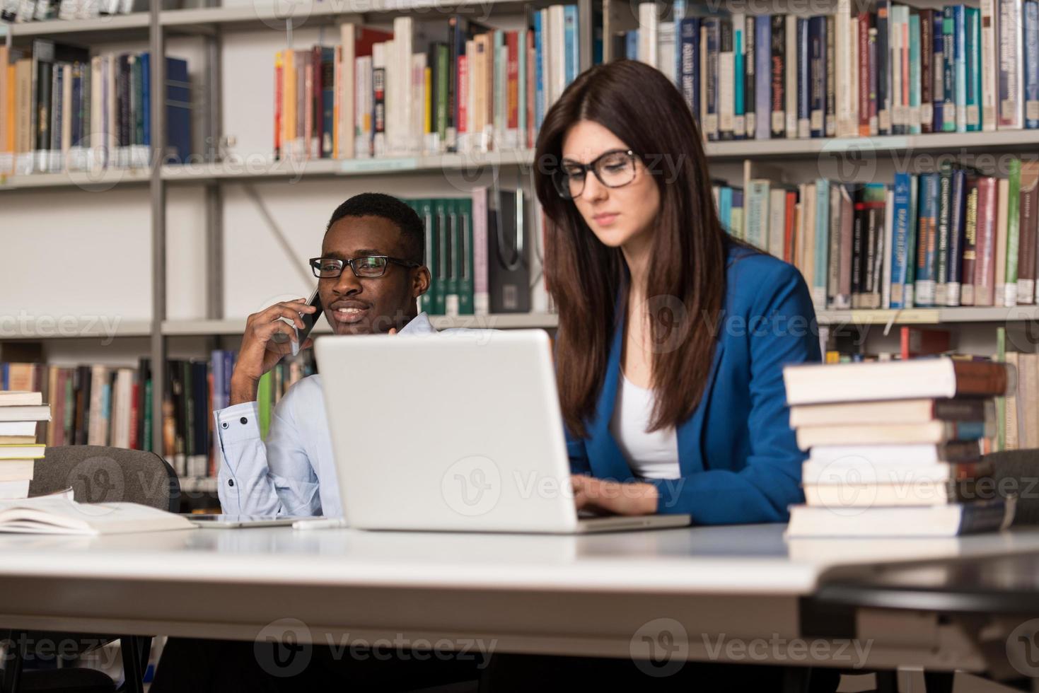 Estudiantes felices trabajando con la computadora portátil en la biblioteca foto