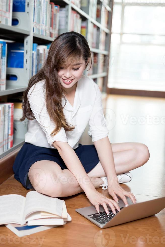 Hermosa estudiante asiática estudiando en la biblioteca con laptop foto