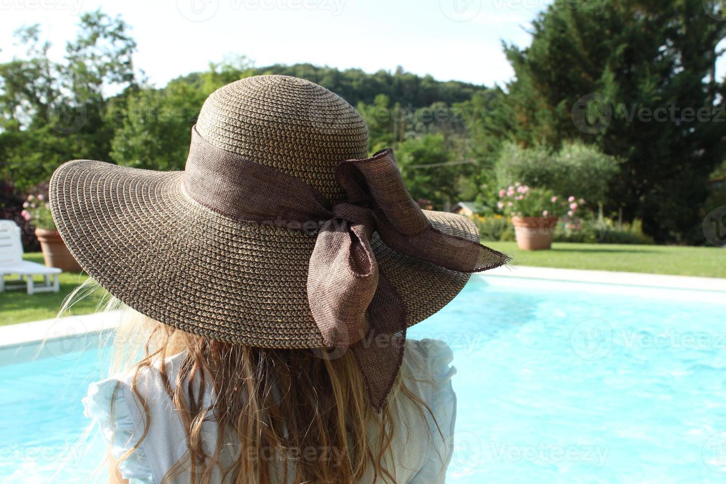 chica de la parte de atrás con sombrero y mirando a una piscina foto