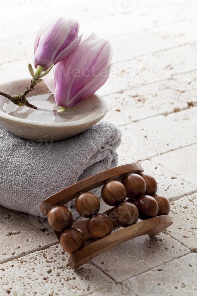 flores de magnolia en una taza de piedra de agua para masaje ayurveda foto