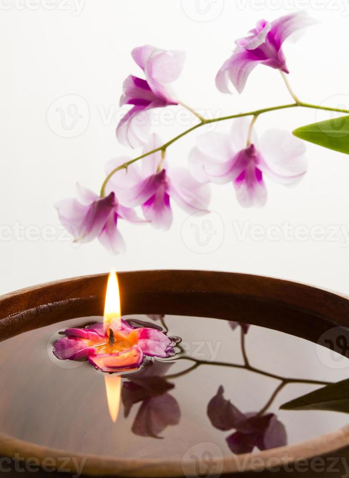 spa concept with candle in wooden bowl. photo