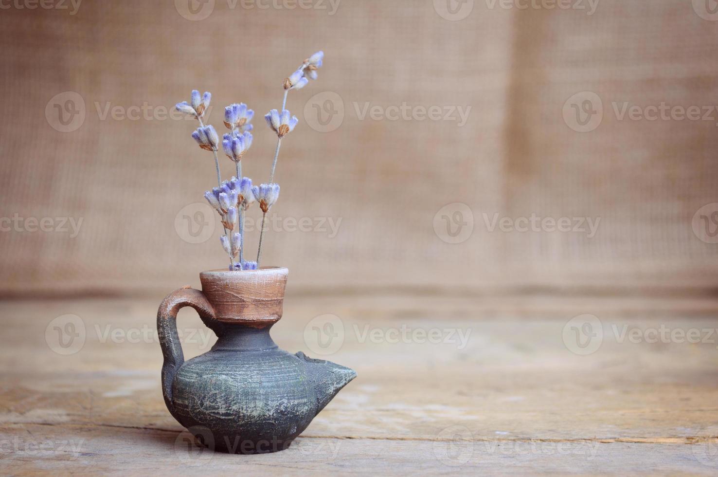 Lavender flower in bottle on wooden table photo