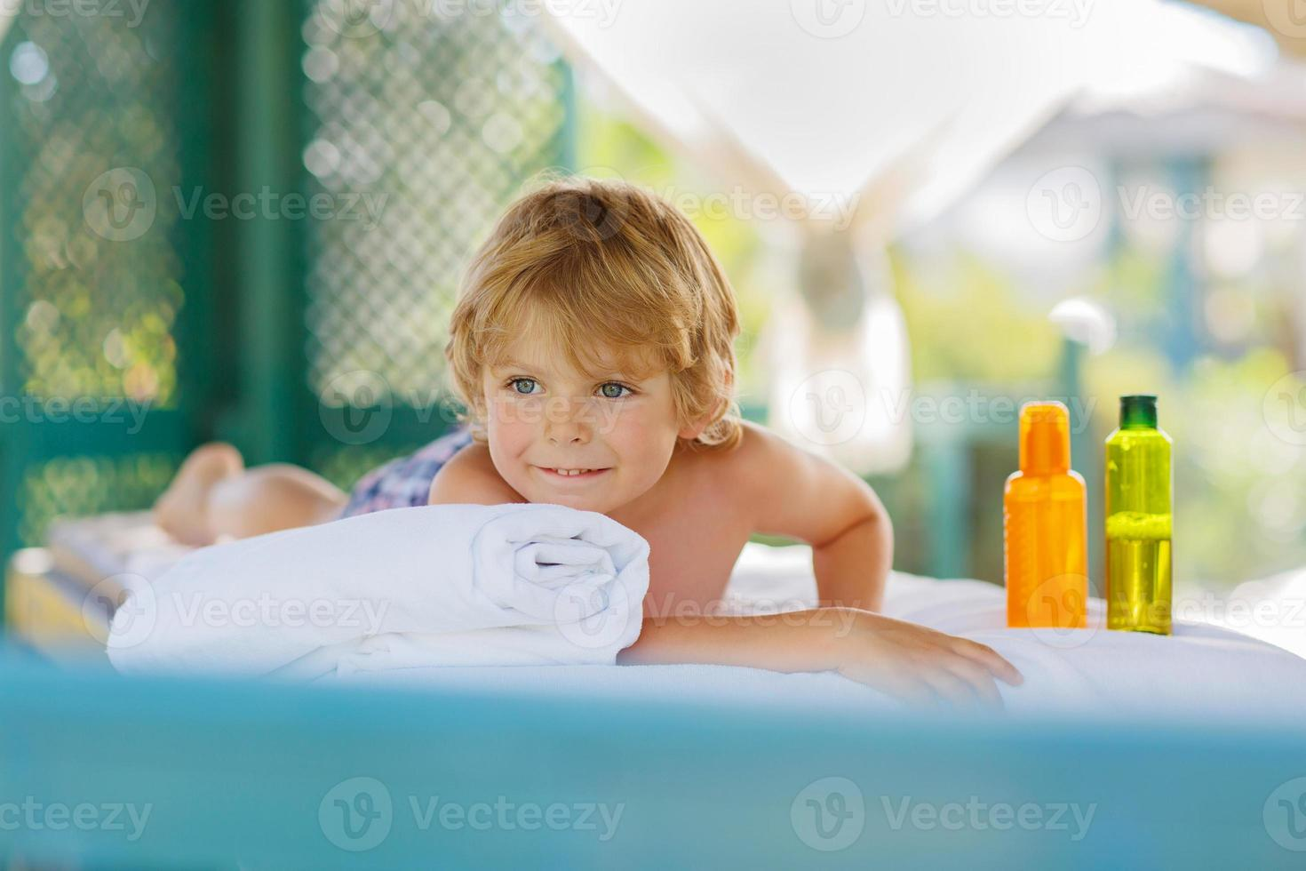 Little kid boy relaxing in spa with having massage photo
