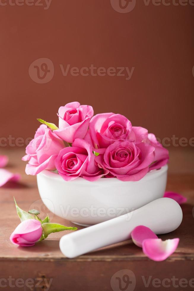 mortar with rose flowers for aromatherapy and spa photo