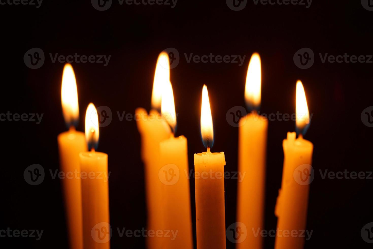 Many burning candles on black photo
