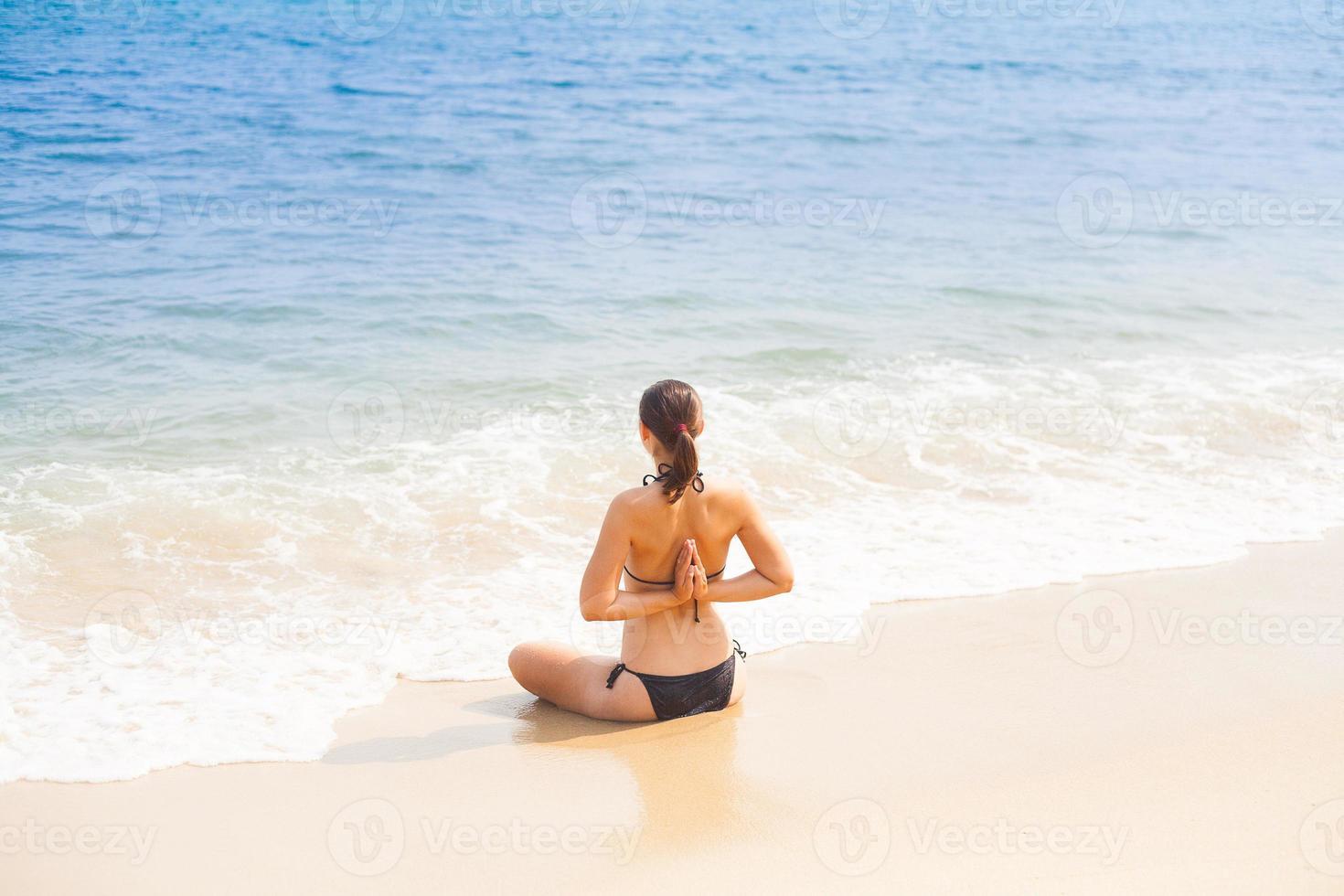 mujer caucásica practicando yoga en la playa foto