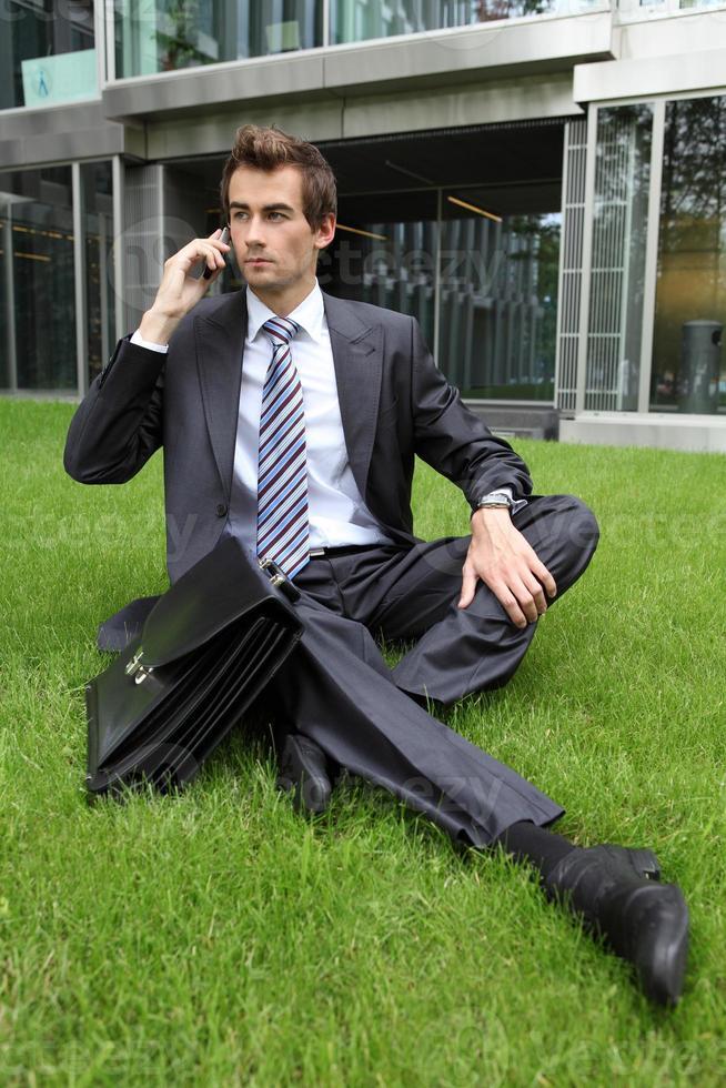 jovem empresário caucasiano sentado na grama foto