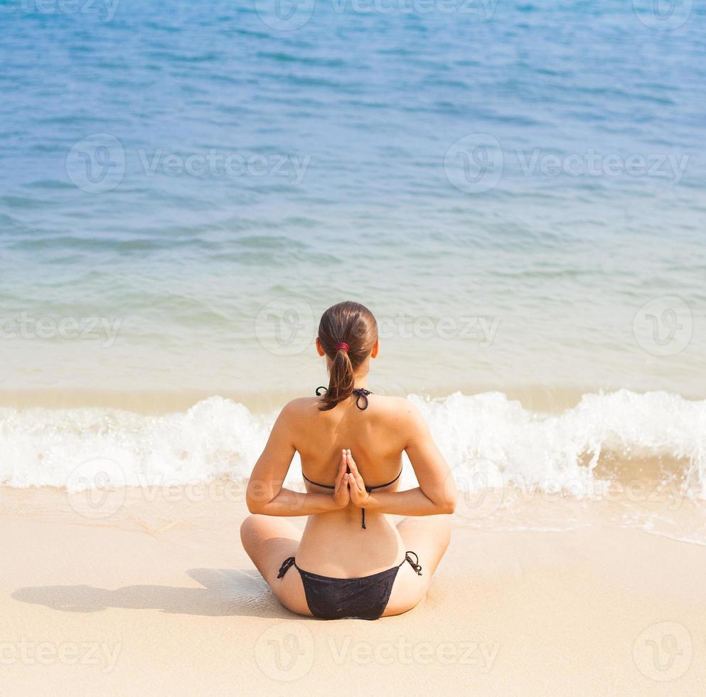 Caucasian woman practicing yoga on beach photo