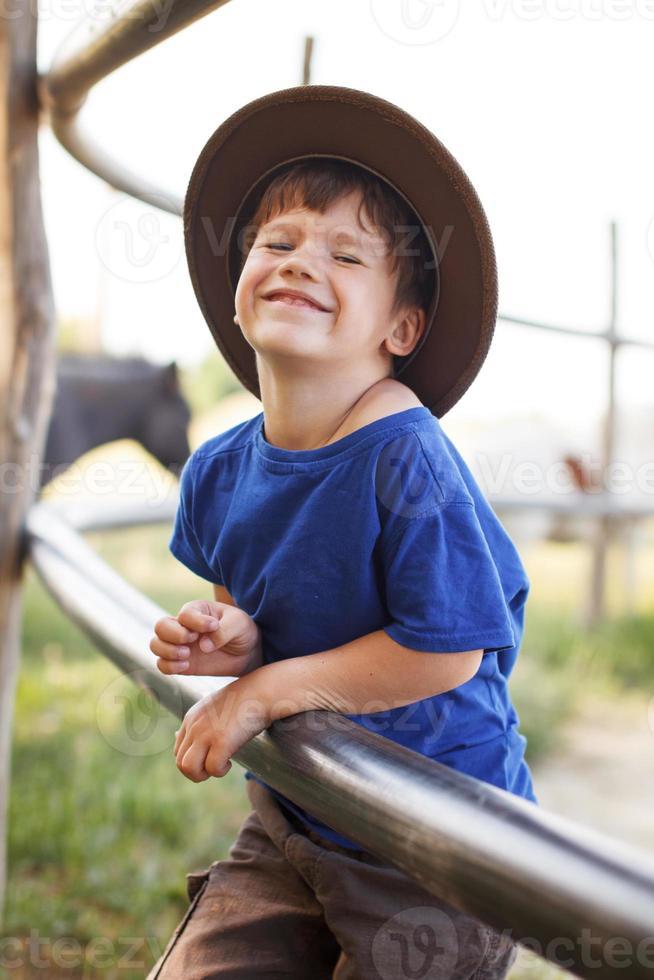 Little caucasian boy laughing on farm photo