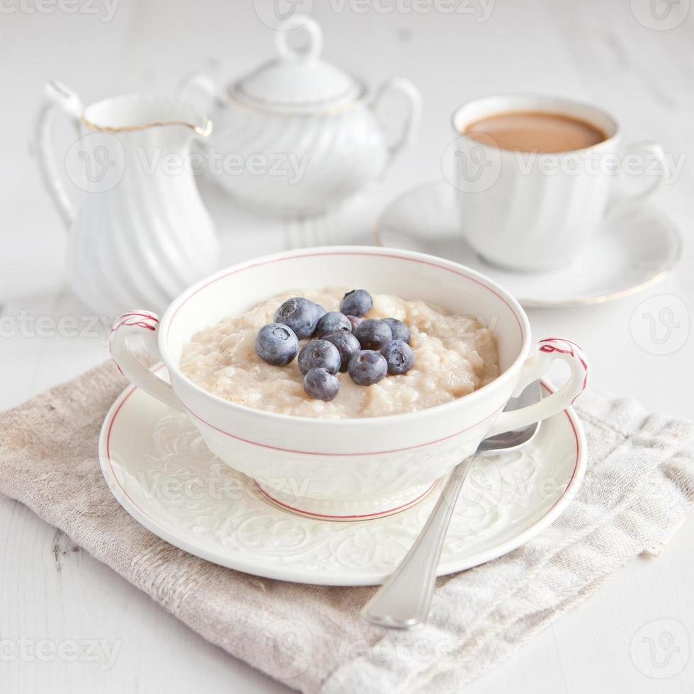 Healthy breakfast: oats porridge with coffee on the table photo