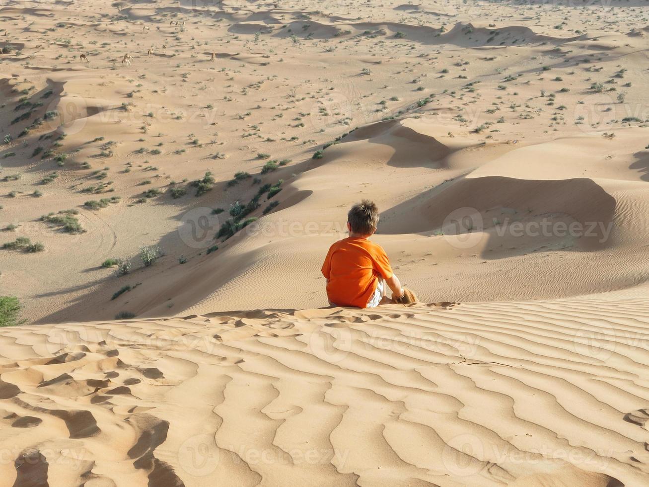 Caucasian boy sitting on sand dune rear view photo