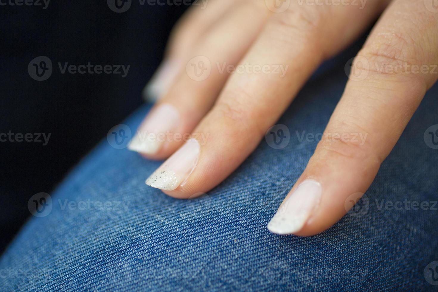 caucasian female hand with light colour nail polish photo