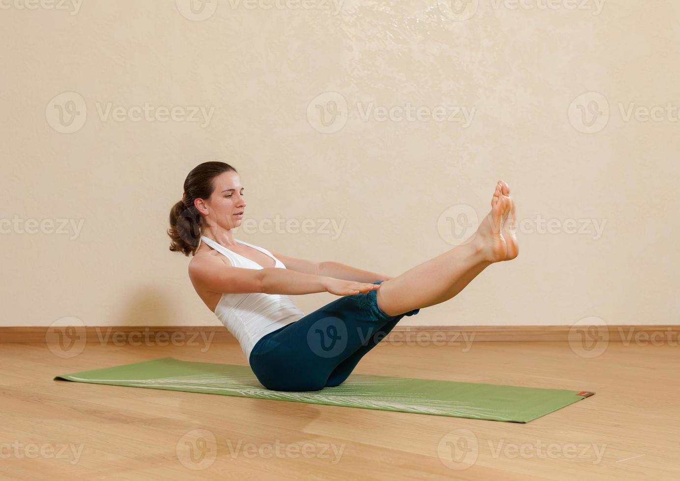 mulher caucasiana está praticando ioga no estúdio (paripurna navasana foto