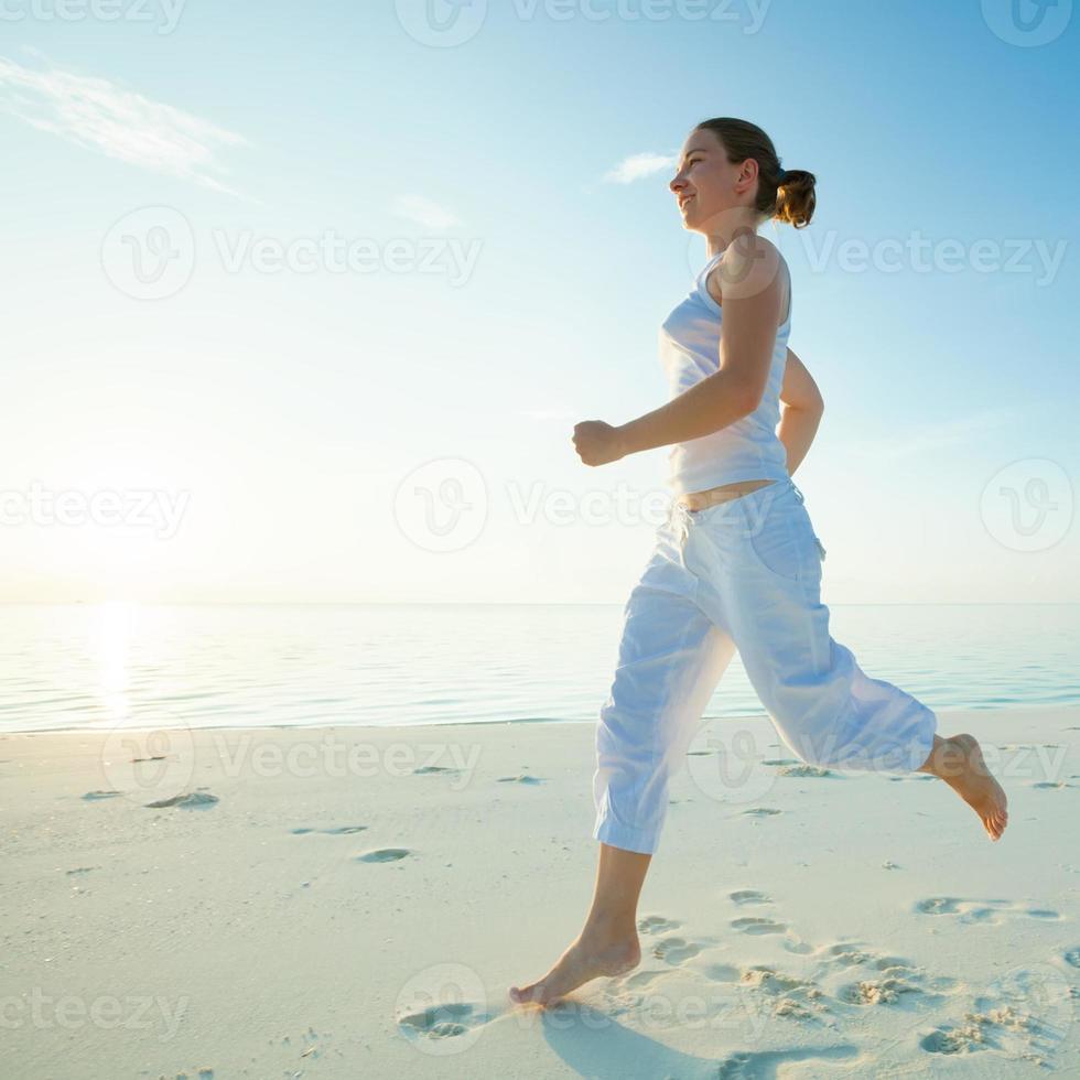 mujer caucásica trotar en la orilla del mar foto