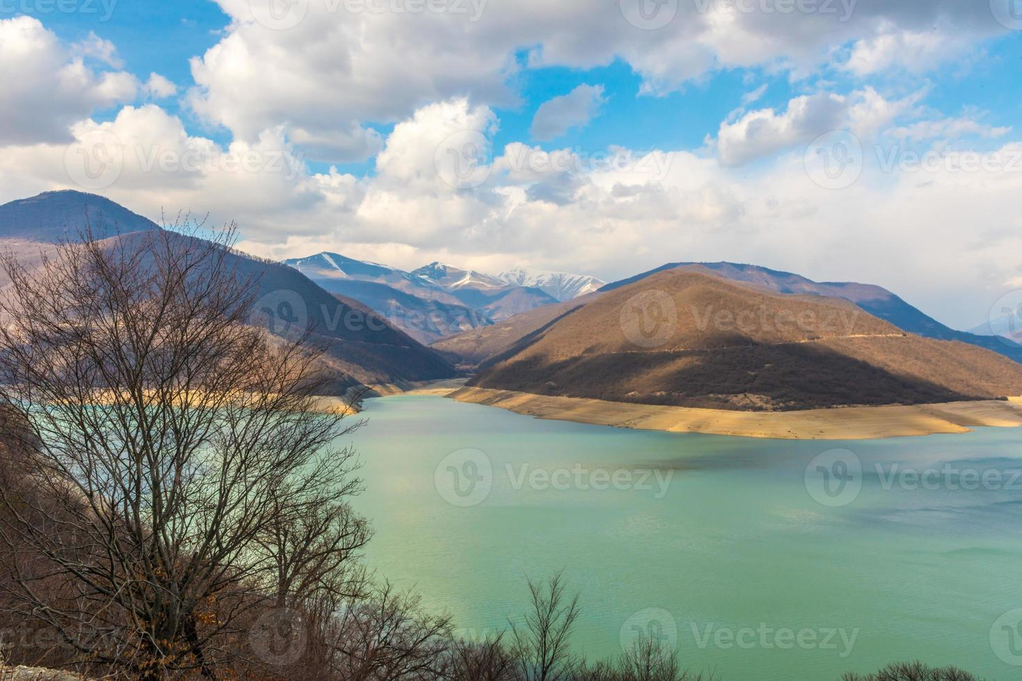 Caucasian mountains near the  green lake and amazing clouds photo