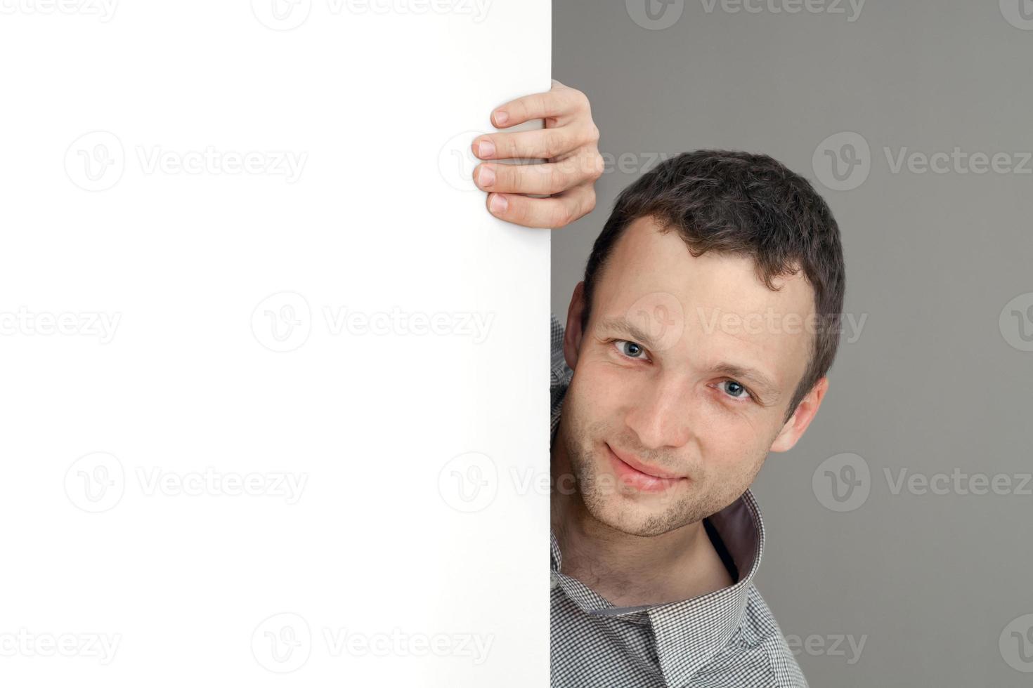 joven sonriente hombre caucásico, retrato de estudio con pared blanca foto