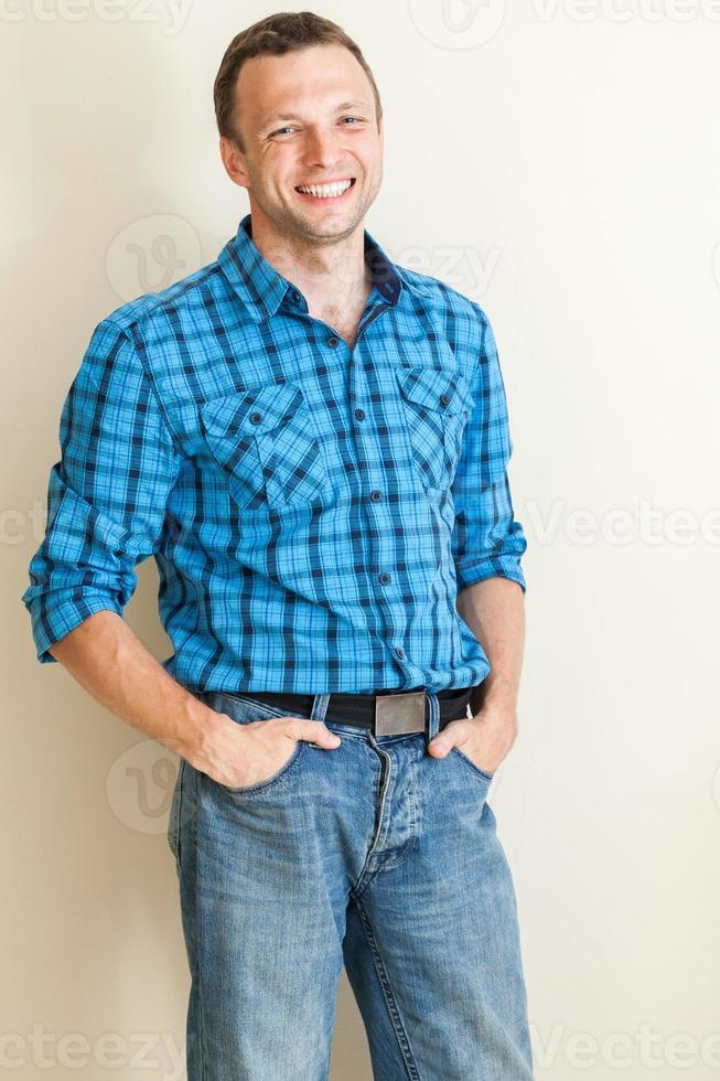 Young positive Caucasian man in casual shirt, studio portrait photo