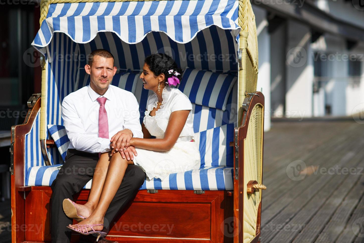 Hermosa mujer india y hombre caucásico, en silla de playa. foto