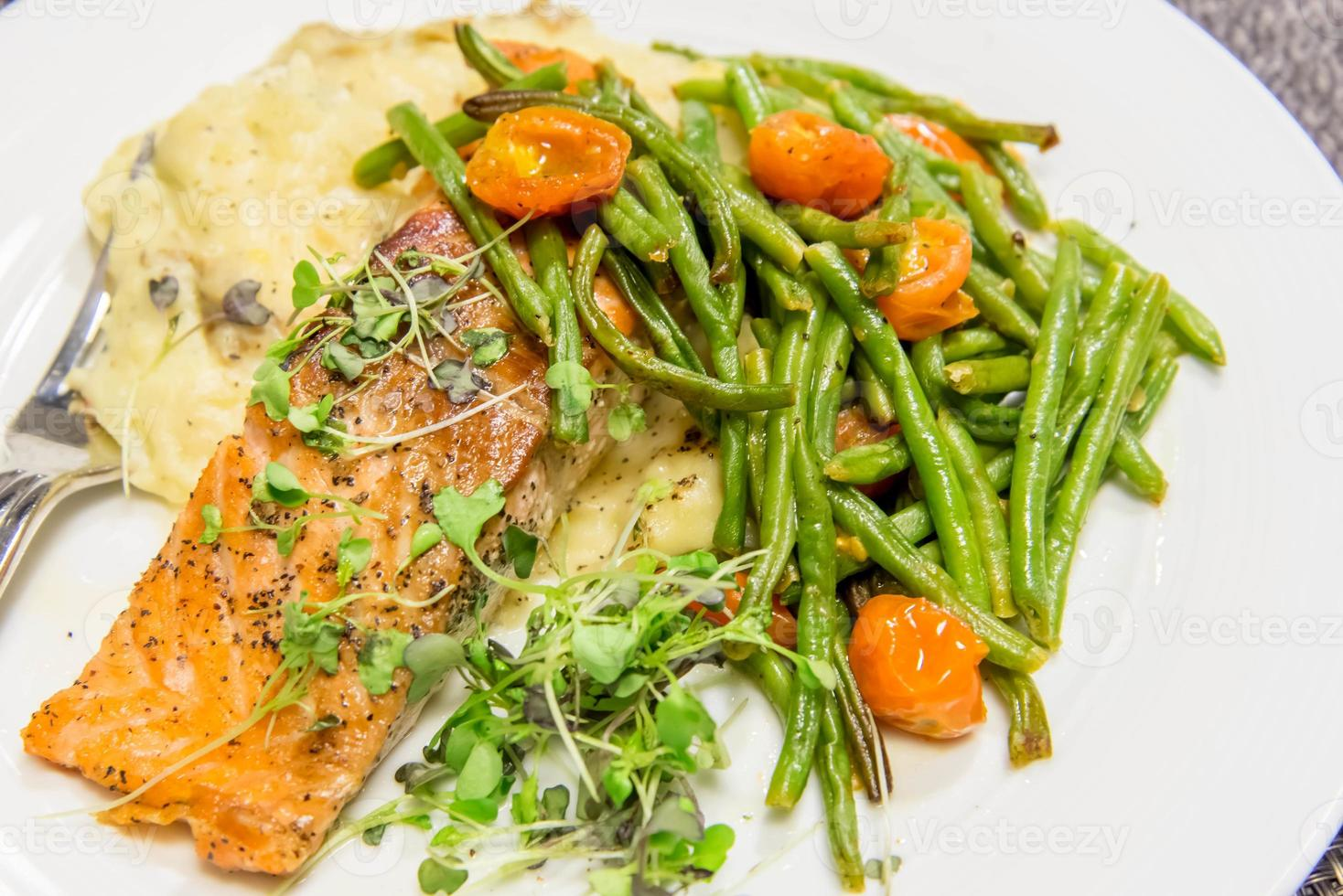 nutritious salmon dinner with green beans and tomatoes photo