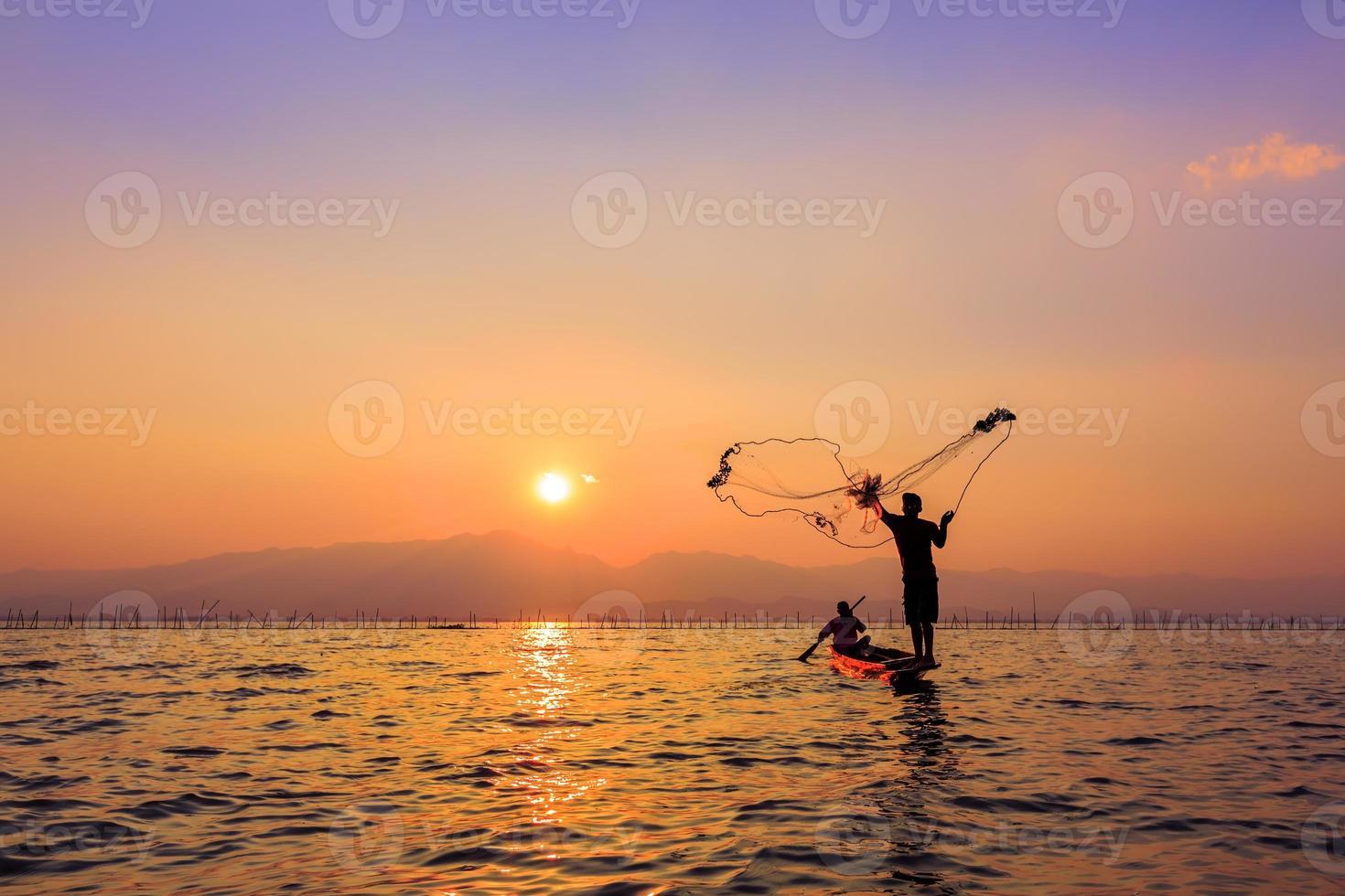 throwing fishing net during sunset , thai photo