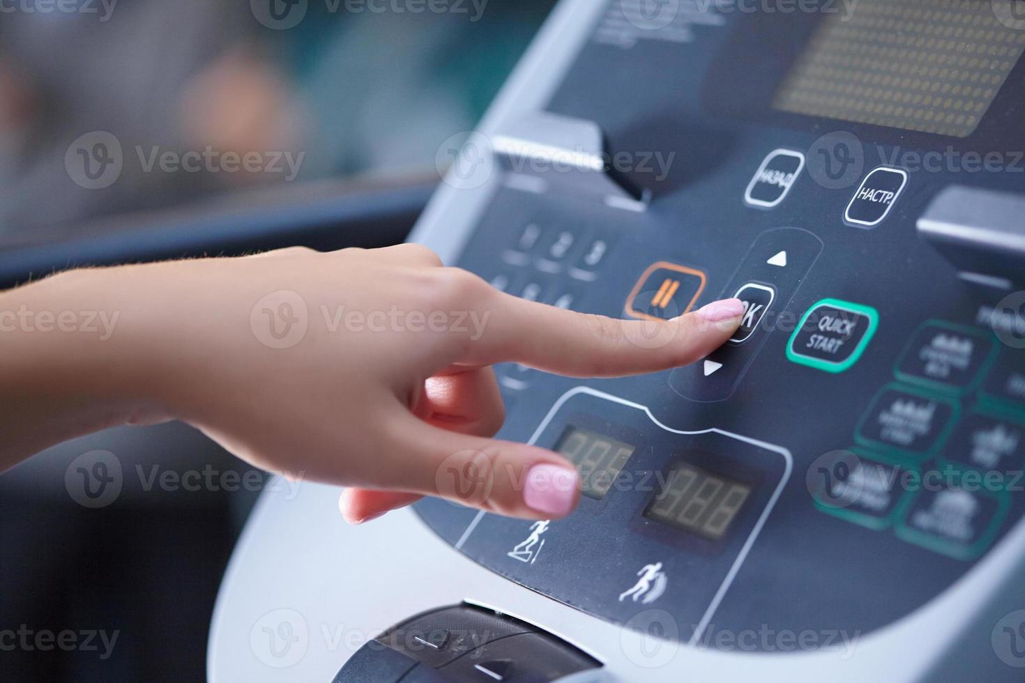girl on a treadmill presses the button photo