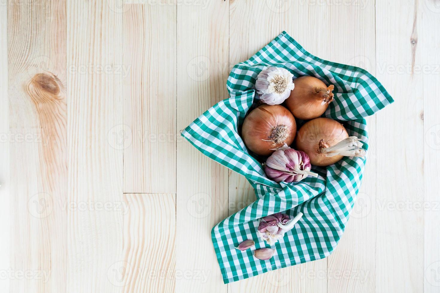 Composición de cebollas y ajo en canasta sobre mesa de madera foto