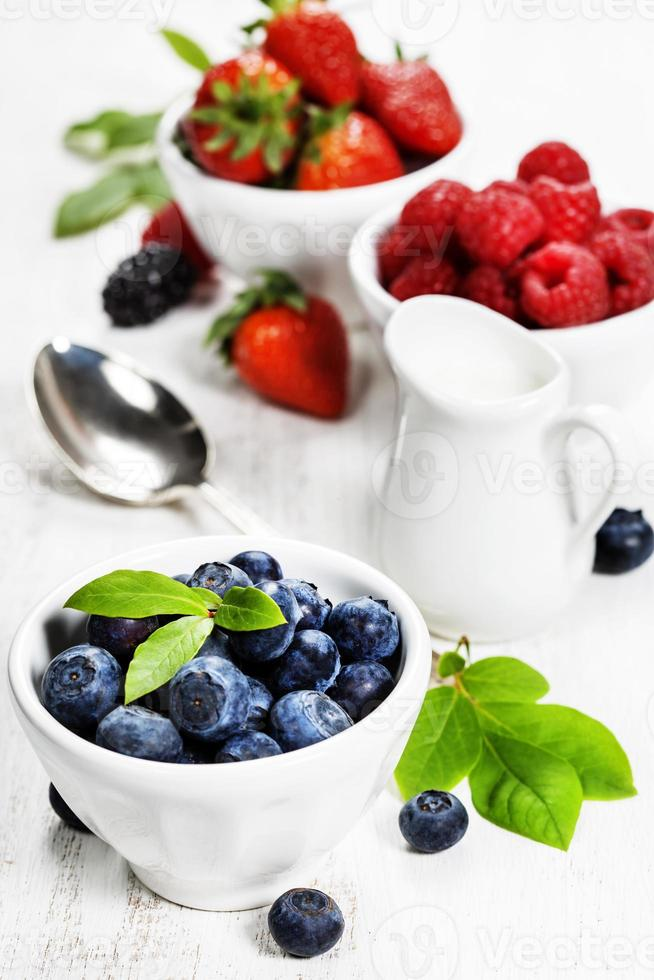 Berries in bowls  on Wooden Background. photo