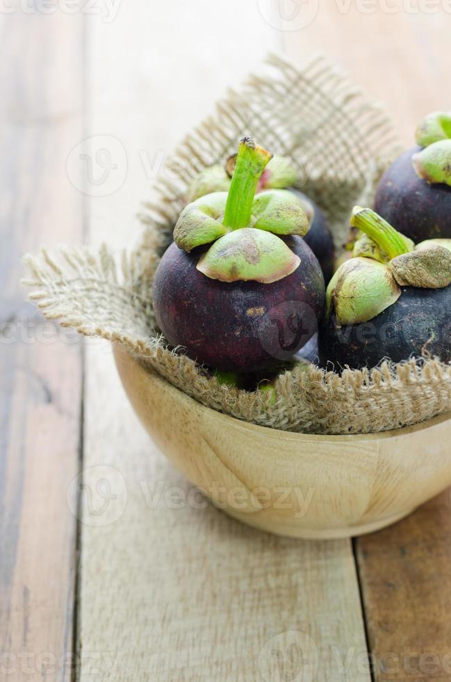 mangoustan dans un bol en bois sur table photo