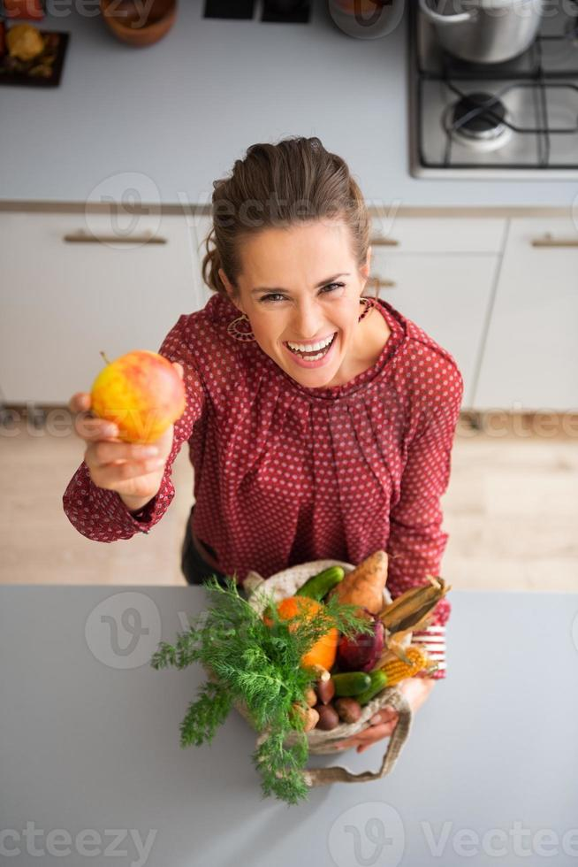 Happy woman holding up apple in kitchen photo