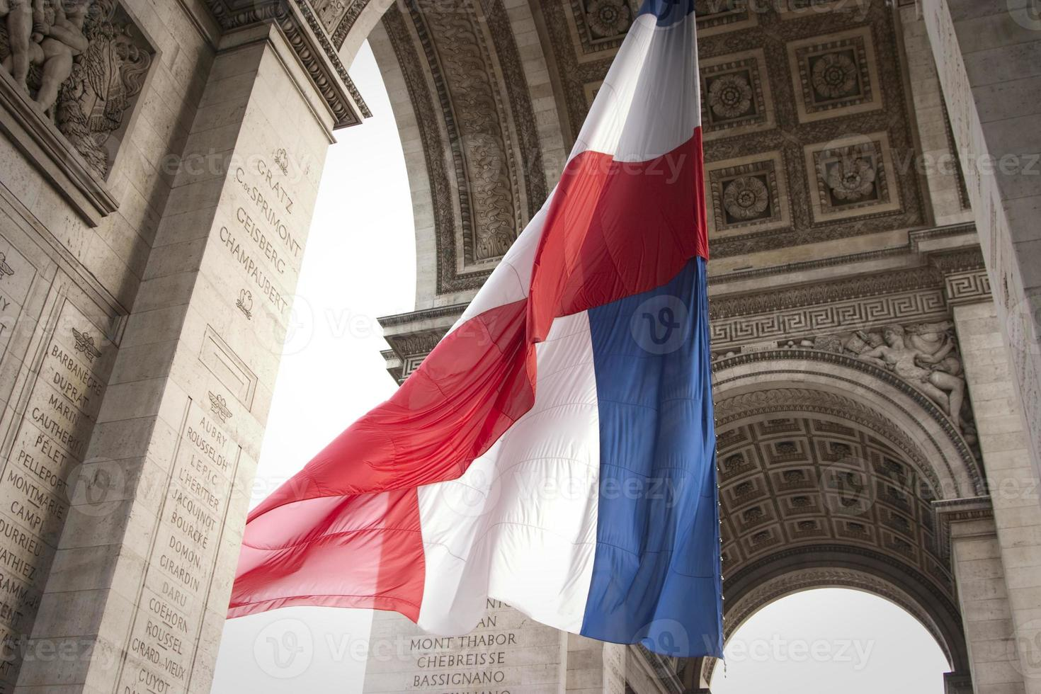 Red white and blue flag waving under a big arch photo