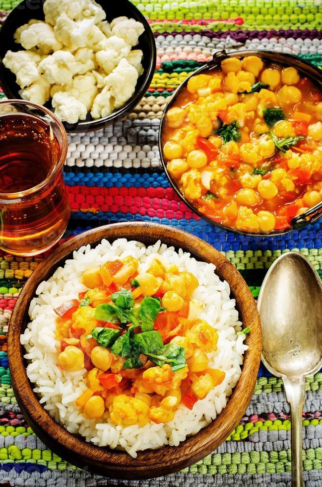 arroz con garbanzos al curry con verduras y pan árabe plano con hierbas foto