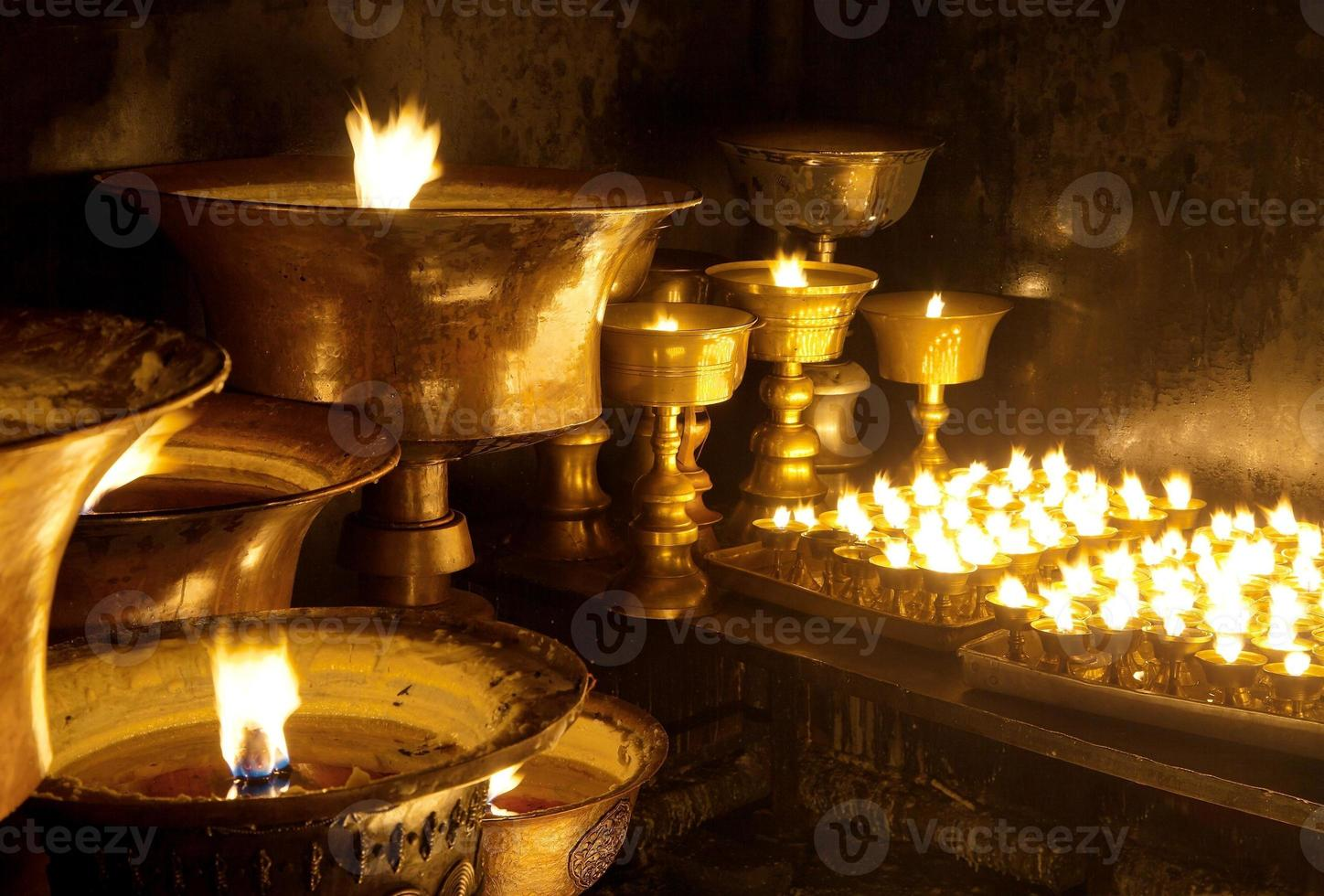 Detail of burning candles in buddhist monastery photo