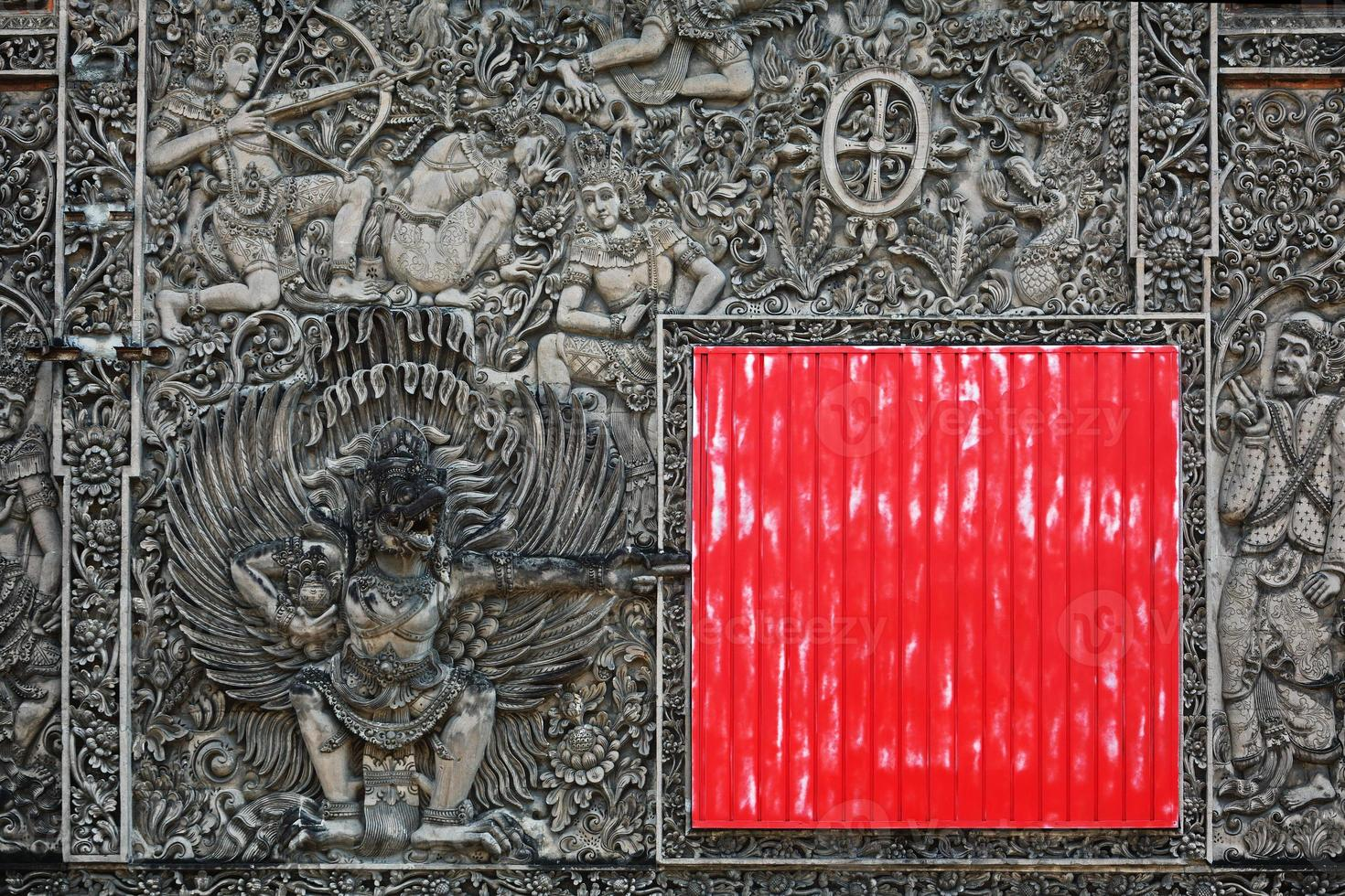 Ancient Balinese stone carving background with the red square shield photo