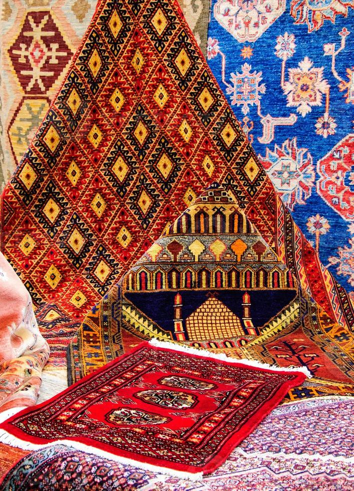 Oriental carpets in market. Mosque image on one of  rugs. photo