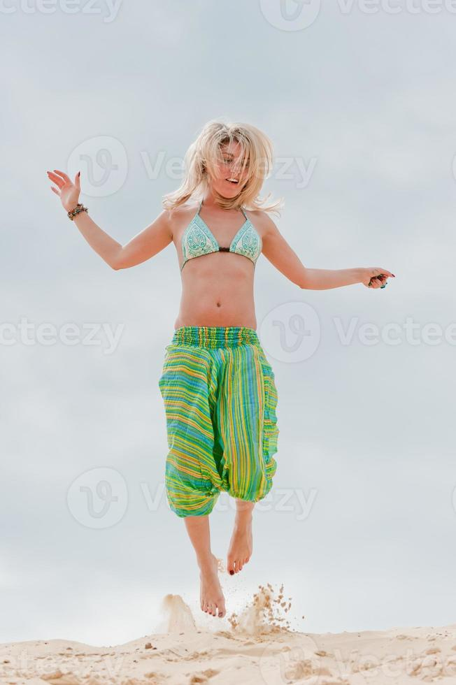 Young slim girl jumping in the sand. photo