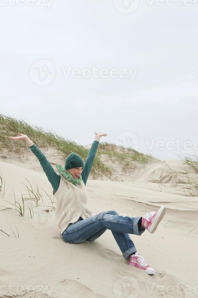 woman with arms up sitting in sand dunes smiling photo