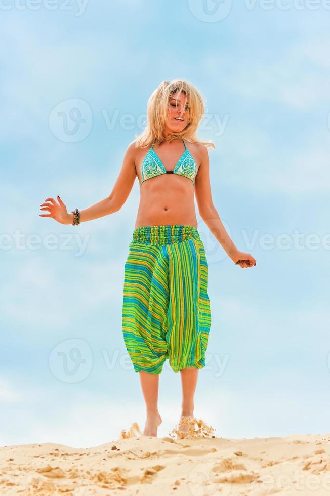 joven delgada saltando en la arena. foto