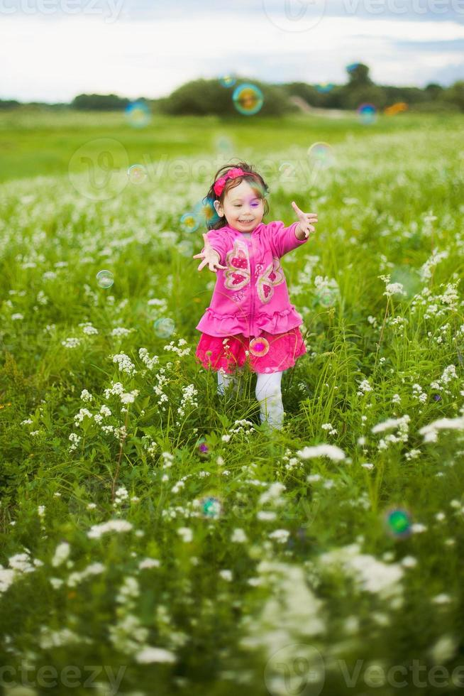 beautiful carefree girl playing outdoors in field photo