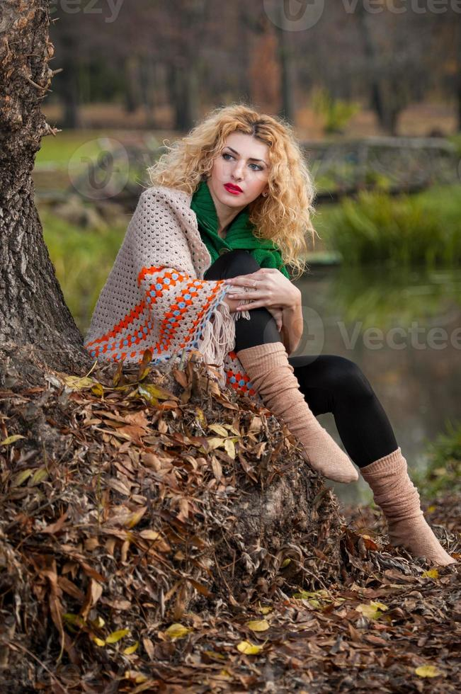 chica rubia con blusa verde y chal grande posando al aire libre foto