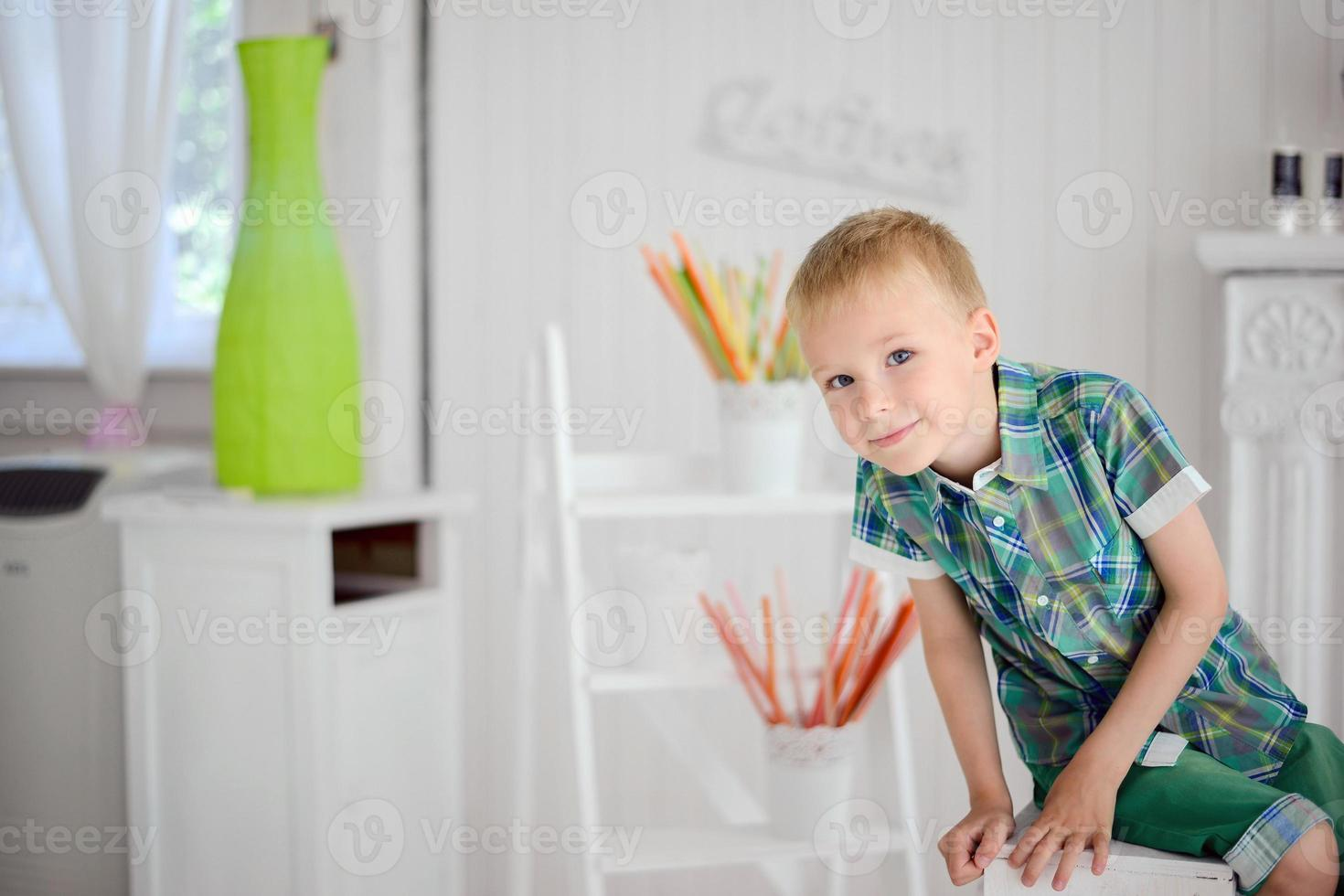 Portrait of happy blond boy child  sitting on chair photo