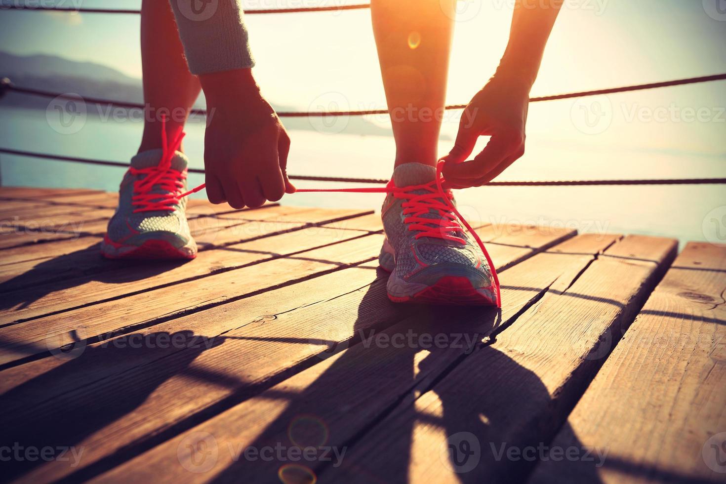 estilo de vida saludable deportes mujer atar cordones de los zapatos foto