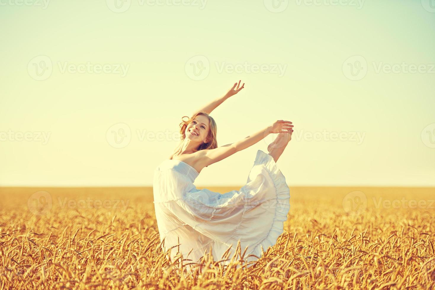 happy young woman enjoying life in golden wheat field photo